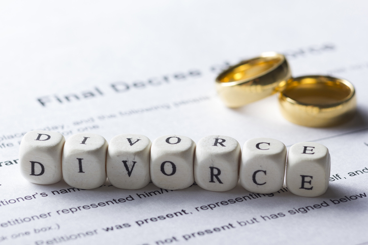 Divorce made up of wooden letters on the table with wedding rings