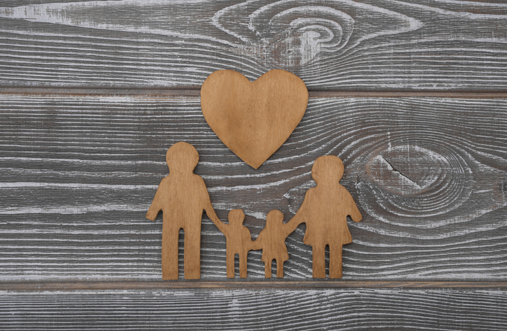 family and heart shape made of wood on a wooden background